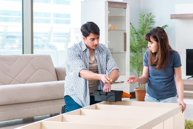 Les meubles se réunissants de jeune famille à la nouvelle maison image libre de droits