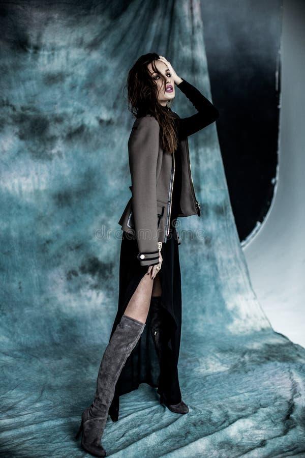 Les militaires de mode dénomment Modelez dans la pose de veste, de jupe et de bottes photo stock