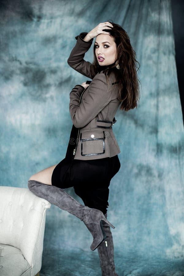 Les militaires de mode dénomment Modelez dans la pose de veste, de jupe et de bottes image libre de droits