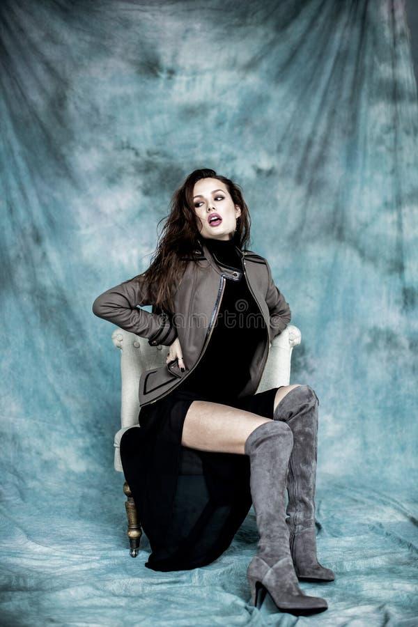 Les militaires de mode dénomment Modelez dans la pose de veste, de jupe et de bottes photographie stock