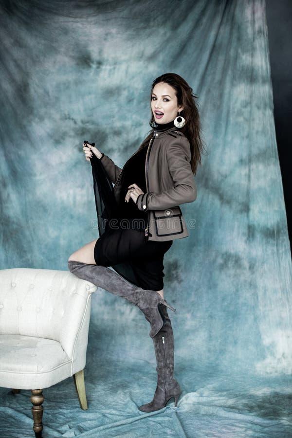 Les militaires de mode dénomment Modelez dans la pose de veste, de jupe et de bottes photos stock