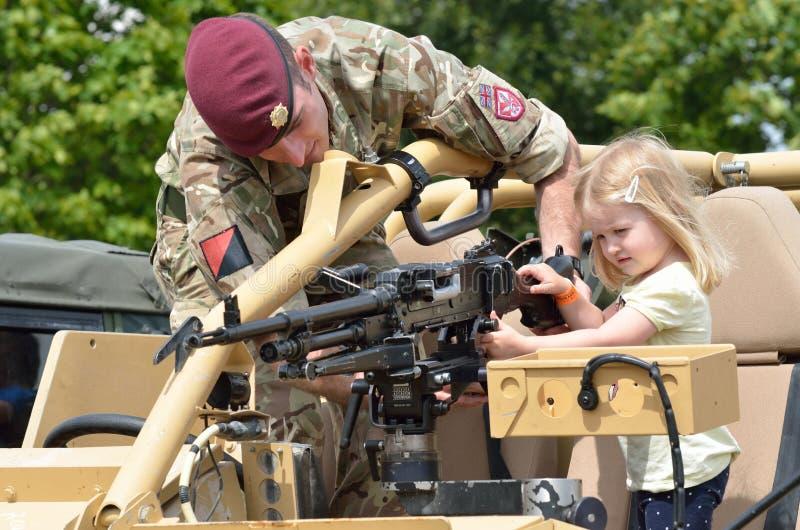 Les militaires tatouent COLCHESTER ESSEX R-U le 8 juillet 2014 : Petite fille étant montrée la mitrailleuse photo stock