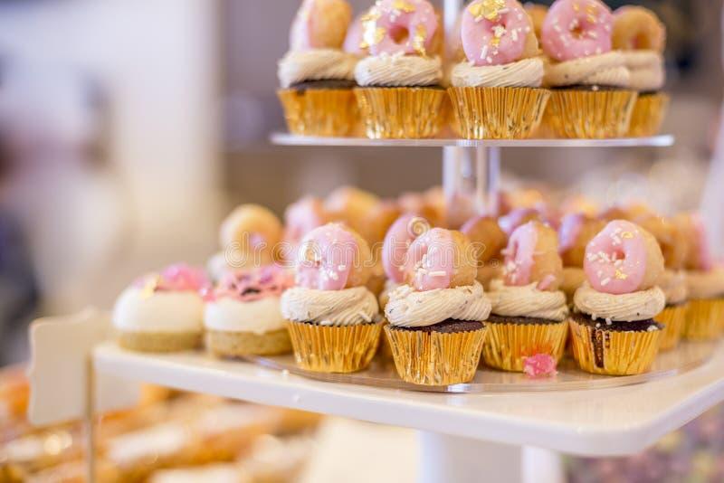 Les mini petits gâteaux de chocolat ont complété avec de mini butées toriques roses sur un desser image stock