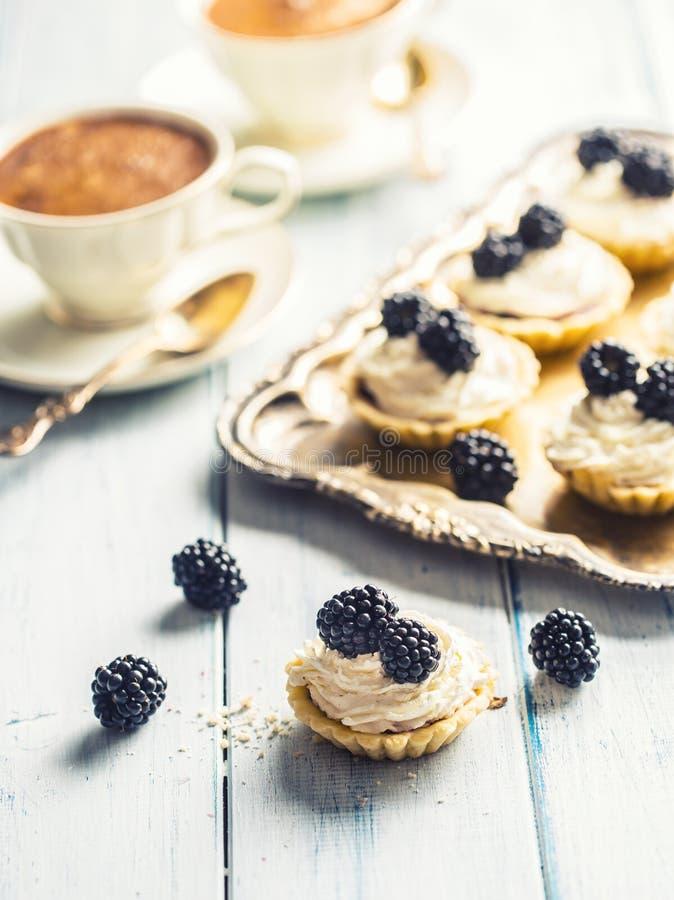 Les mini tartelettes avec des mûres ont fouetté la crème et le café photo libre de droits
