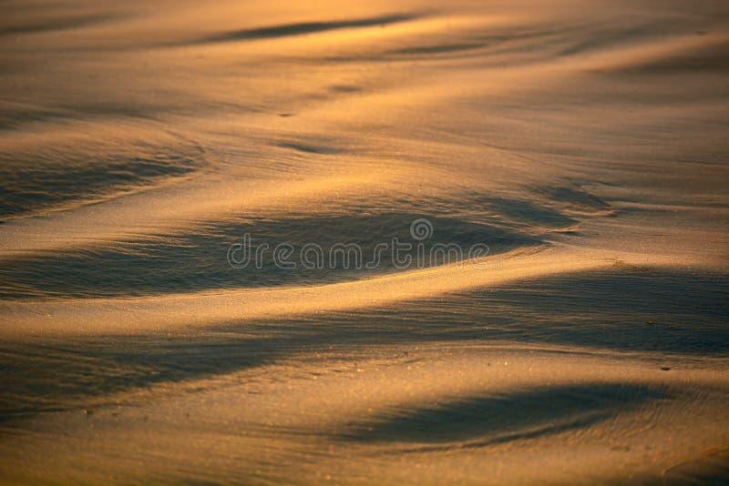 Les modèles abstraits ont fait par des vagues sur le sable d'or des plages du Nouvelle-Zélande ; début de la matinée - belle lumi image libre de droits
