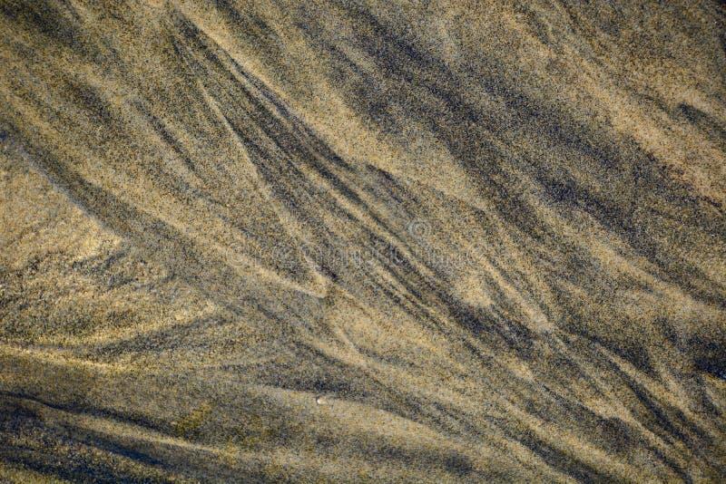 Les modèles abstraits ont fait par des vagues sur le sable d'or des plages du Nouvelle-Zélande ; début de la matinée - belle lumi photos stock