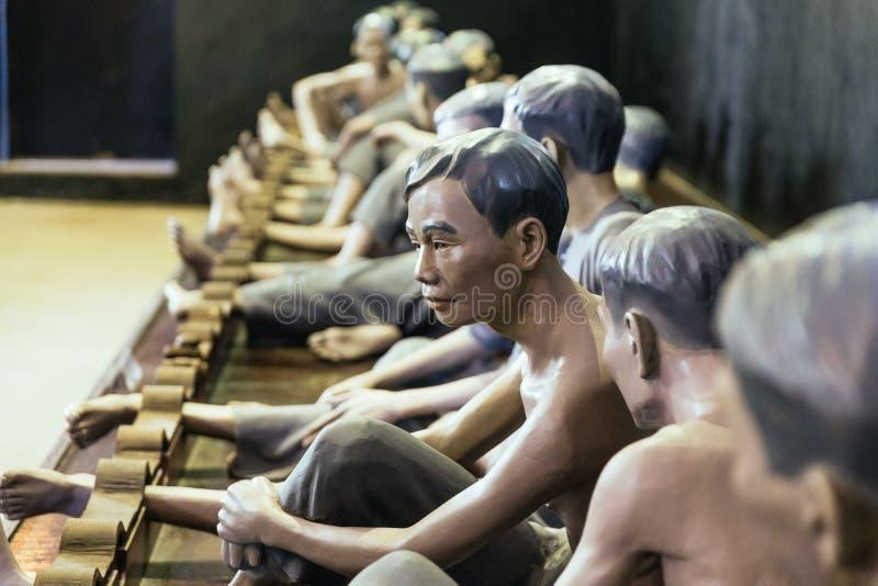Les modèles des prisonniers détenus par la serrure leur cheville de pied sur quelque chose aiment la console en bois au musée de  photographie stock libre de droits