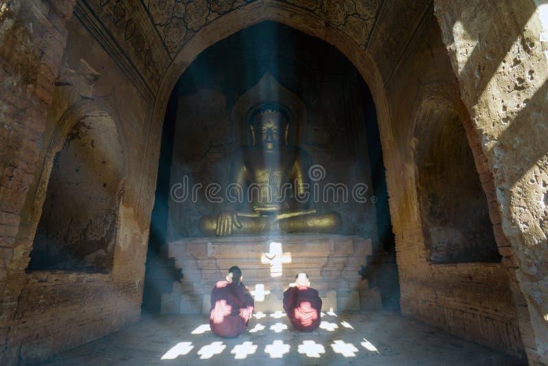 Les moines d'enfant prient à l'intérieur d'une pagoda - Bagan, Myanmar images stock