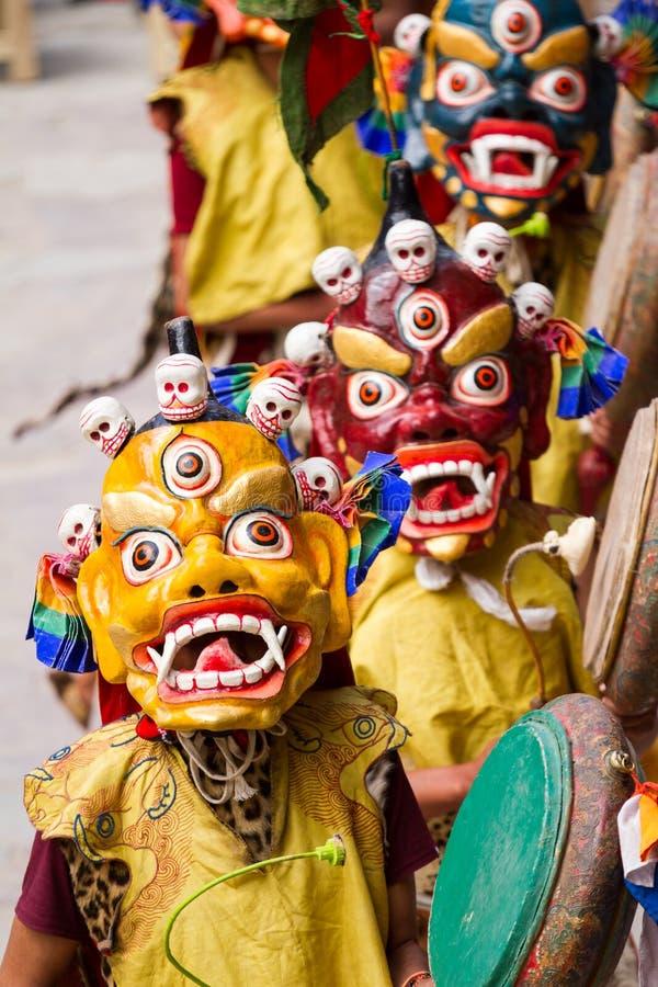 Les moines non identifiés avec des tambours exécute une danse masquée et costumée religieuse de mystère de bouddhisme tibétain image stock