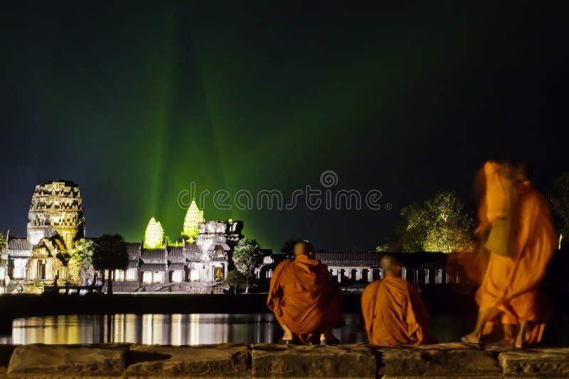 Les moines observent la lumière de soirée afficher aux ruines d'Angkor image libre de droits
