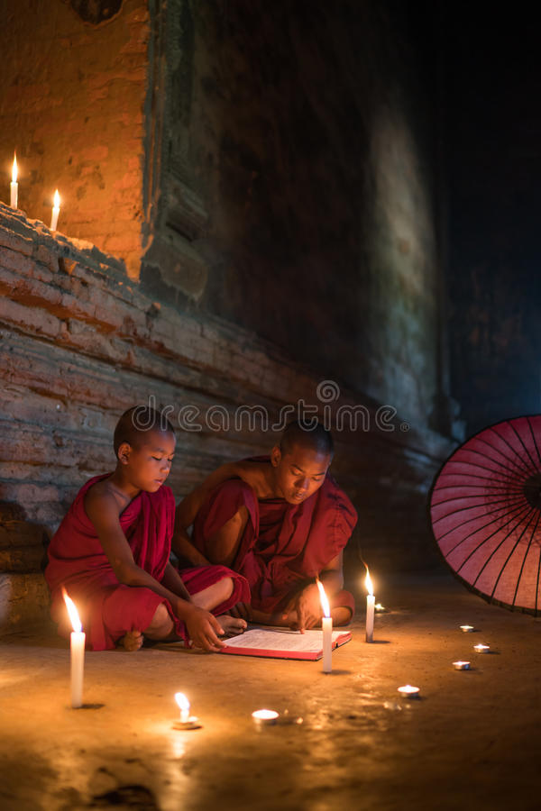 Les moines s'asseyant sur le scripture de lecture de plancher réservent photographie stock