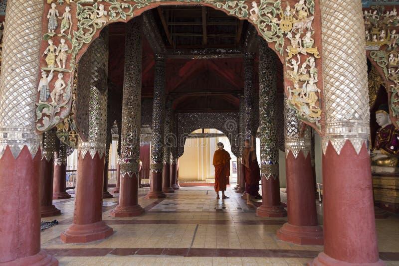 Les moines se sont habillés dans des robes longues visitant le temple richement décoré d'Ananda dans Bagan photographie stock libre de droits