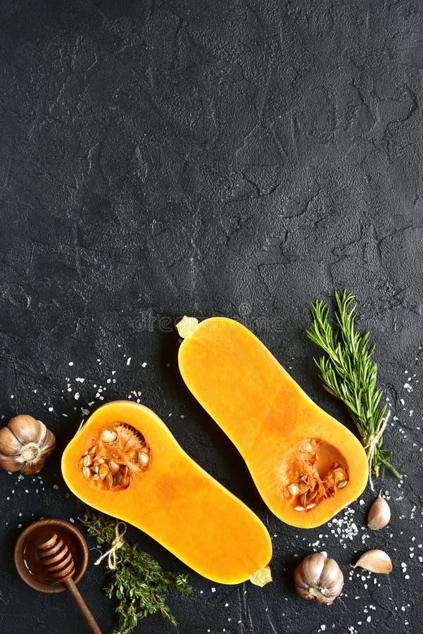 Les moitiés de la courge de butternut organique crue avec des épices et ingredien images stock