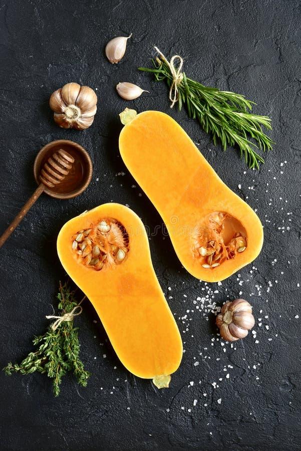 Les moitiés de la courge de butternut organique crue avec des épices et ingredien image stock