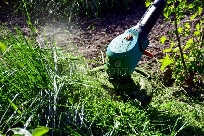 Les moments simples de la vie, travail ordinaire dans le jardin - homme ?quilibrant l'herbe avec le trimmer r?sistant dans le jar images stock
