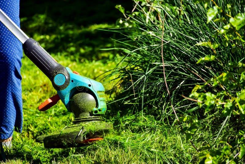 Les moments simples de la vie, travail ordinaire dans le jardin - homme ?quilibrant l'herbe avec le trimmer r?sistant dans le jar images libres de droits