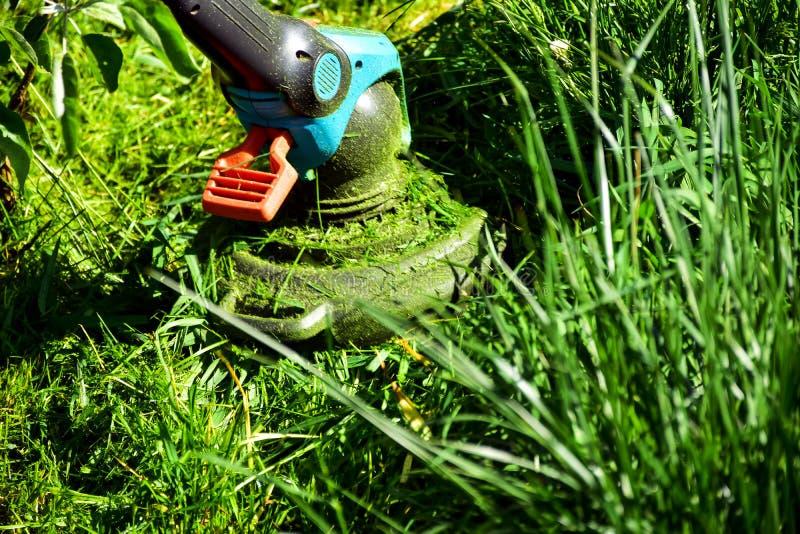 Les moments simples de la vie, travail ordinaire dans le jardin - homme ?quilibrant l'herbe avec le trimmer r?sistant dans le jar photos stock