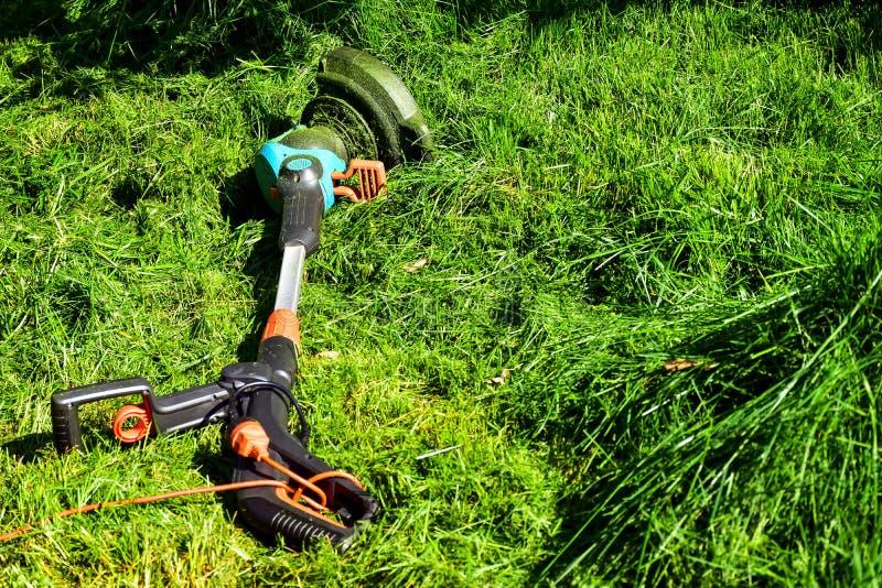 Les moments simples de la vie, travail ordinaire dans le jardin - homme ?quilibrant l'herbe avec le trimmer r?sistant dans le jar photographie stock