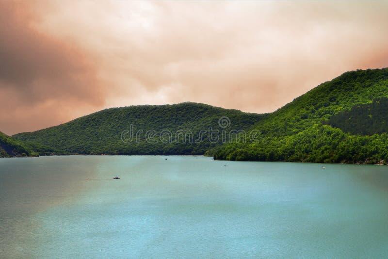 Les montagnes avec la forêt verte sur un lac étayent sur le ciel orageux jaune avec le fond de nuages photographie stock libre de droits