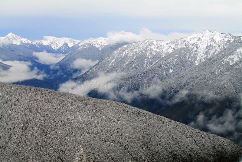 Les montagnes couronnées de neige au delà de la neige ont couvert des collines image libre de droits