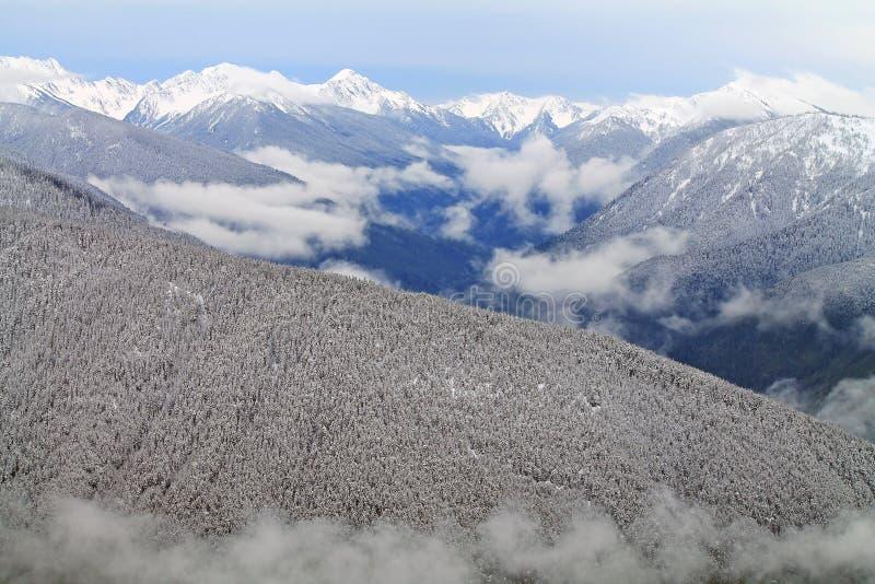 Les montagnes couronnées de neige au delà de la neige ont couvert des collines images stock