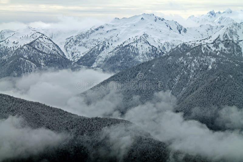 Les montagnes couronnées de neige au delà de la neige ont couvert des collines images libres de droits