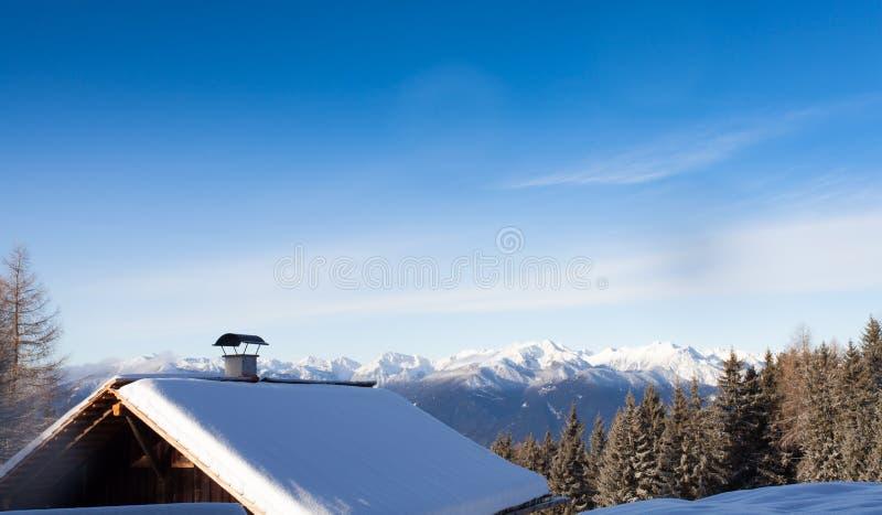 Les montagnes du sud de neige du Tirol aménagent en parc et la carlingue en bois photographie stock libre de droits