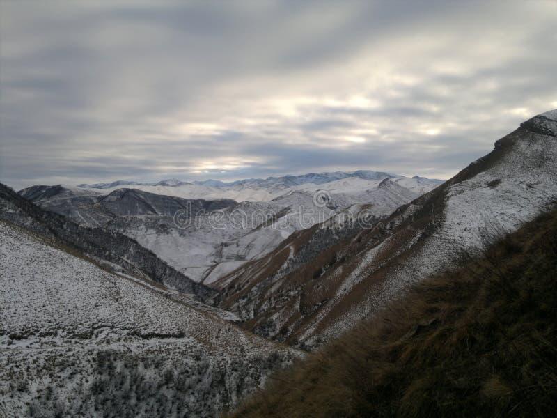 Les montagnes La neige de observation de femme a couvert des montagnes images stock
