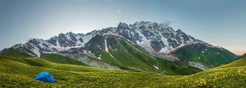 Les montagnes panoramiques aménagent en parc avec la tente dans le camp de touristes sur la vallée herbeuse de montagne Hausse en photo stock