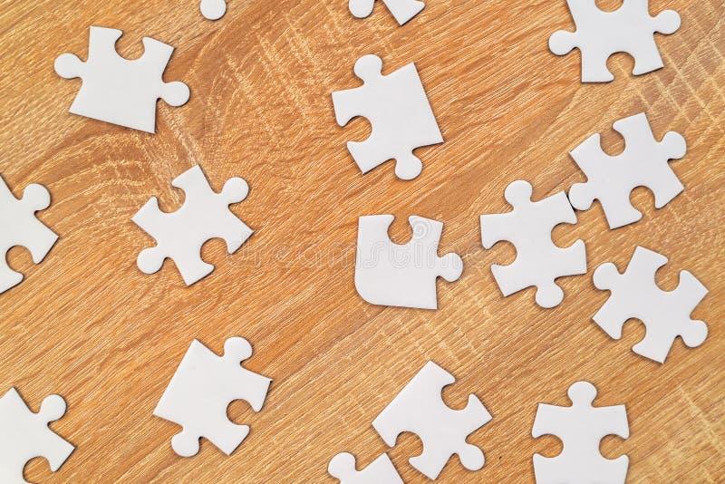Les morceaux blancs de puzzle denteux ont dispersé sur la table en bois photo libre de droits