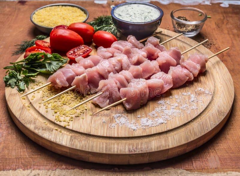 Les morceaux crus de poulet sur des brochettes sur un hachoir avec des légumes d'herbes sauce sur la fin en bois de fond  images stock