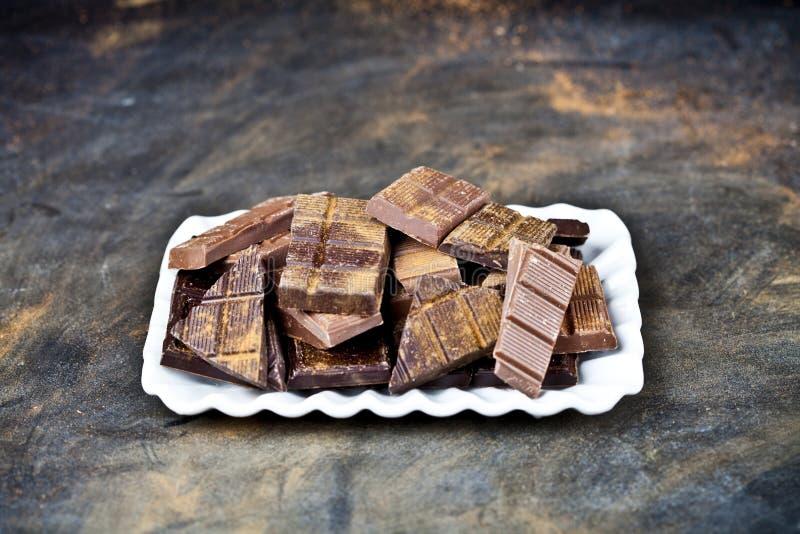 Les morceaux de barre de chocolat amassent la poudre de cannelle de witn du plat en c?ramique blanc Concept doux de photo de nour photographie stock libre de droits