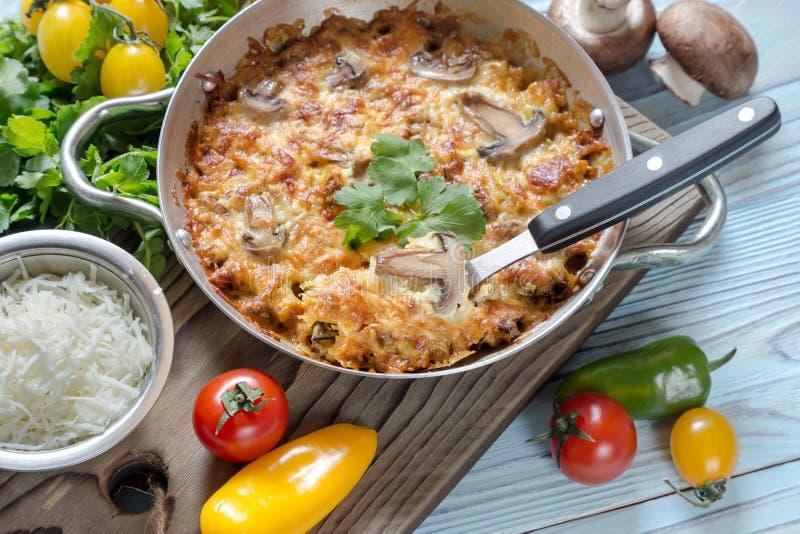 Les morceaux de blanc de poulet ont fait cuire au four avec les champignons et le fromage photo libre de droits