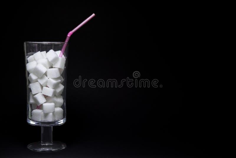 Les morceaux du sucre rapièce dans un verre avec une paille photographie stock libre de droits