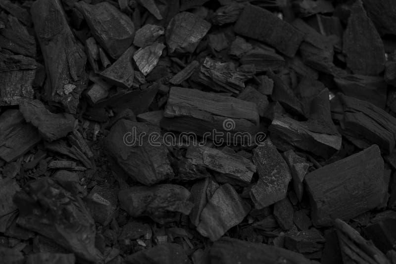Les morceaux noirs de charbon de bois donnent au fond une consistance rugueuse pour le barbecue photo stock