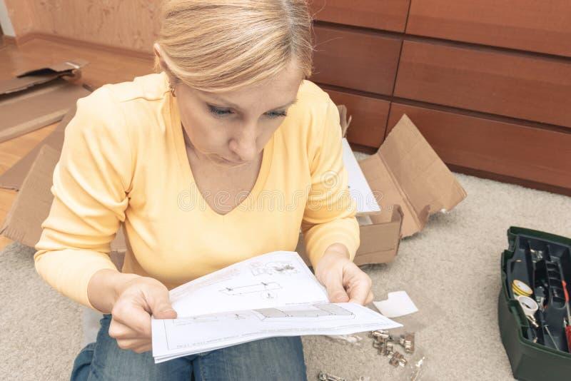 Les morceaux se r?unissants de jeune femme c?libataire de nouveaux meubles et de lire l'instruction, les bo?tes ouvertes avec des photos stock