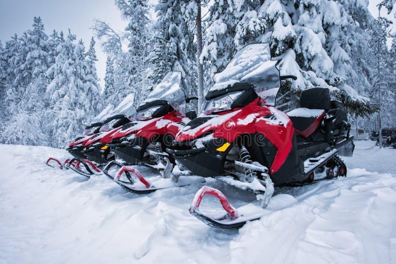 Les motoneiges rouges et noirs s'approchent de la forêt en hiver image libre de droits