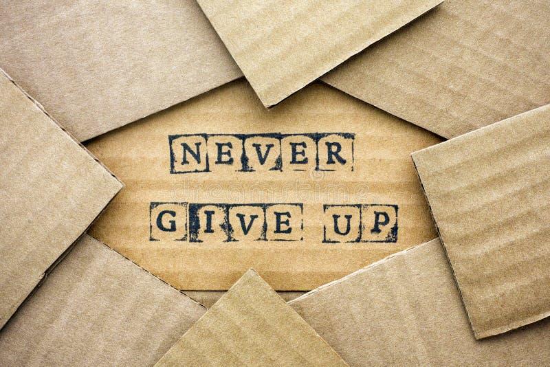 Les mots Give Up ne font jamais par les timbres noirs d'alphabet sur le carton image libre de droits