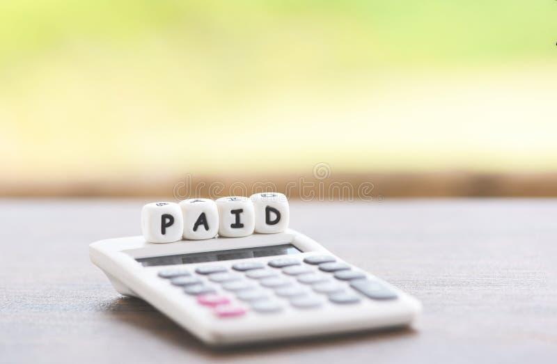 Les mots payés et la calculatrice sur la table pendant le temps ont payé le paiement aux affaires de bureau images libres de droits