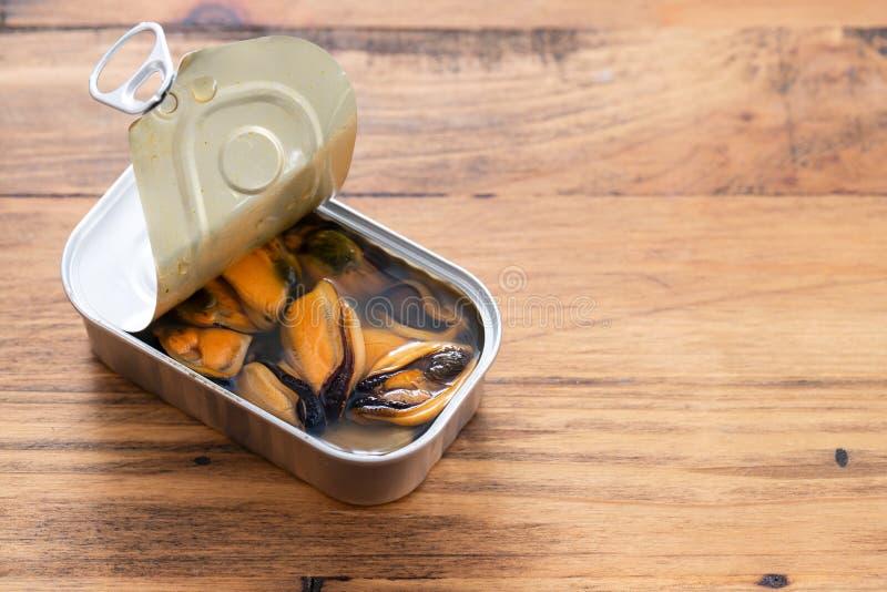 Les moules ont mis en boîte la nourriture sur le fond en bois photographie stock libre de droits