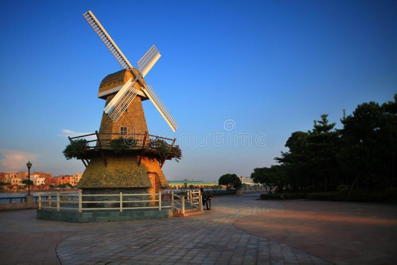 Les moulins à vent de bâtiment dans le coucher du soleil images libres de droits