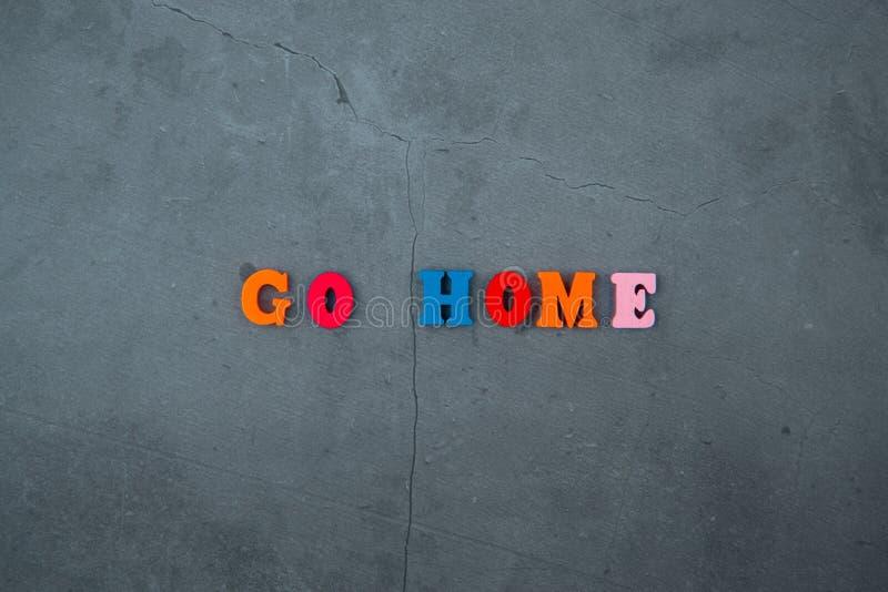 Les multicolores rentrent à la maison mot sont faits de lettres en bois sur un fond plâtré gris de mur photographie stock libre de droits