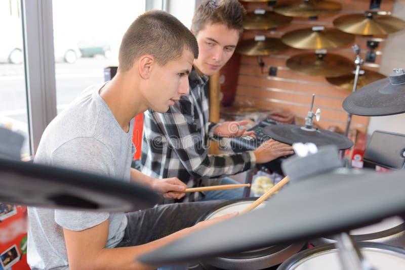 Les musiciens d'amis avec l'essai bat du tambour au magasin de musique photos libres de droits