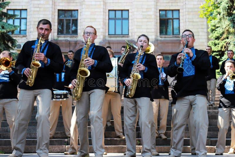 Les musiciens d'orchestre de vent dans des chemises brod?es ukrainiennes noires jouent des saxophones et des cannelures ? un fest photo stock