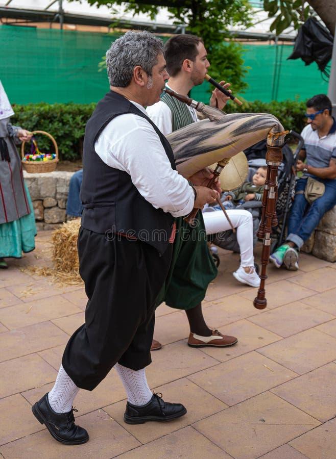 Les musiciens et les danseurs dans des costumes nationaux exécutent pour des touristes et des citoyens à la foire de village, Esp images stock