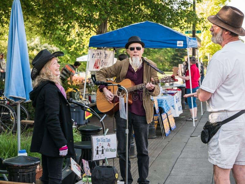 Les musiciens locaux causent avec des amis au marché d'agriculteurs de Corvallis, O image libre de droits
