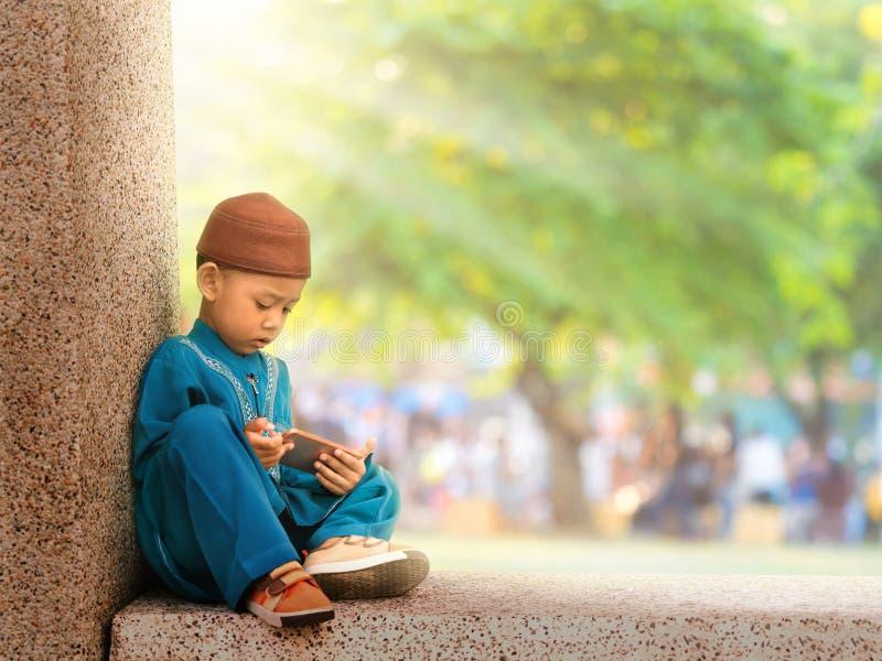 les musulmans heureux badinent avec le téléphone intelligent jouant de cérémonie images stock