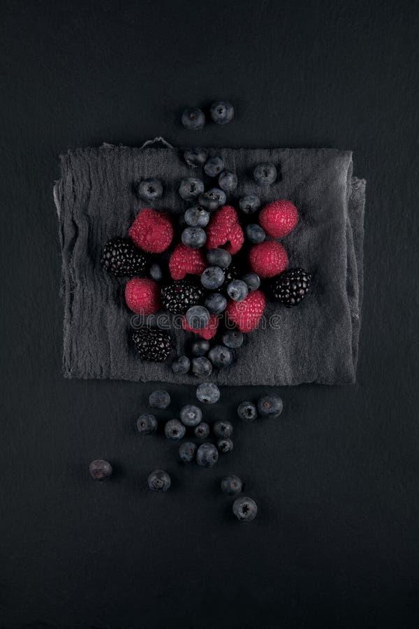 Les myrtilles, les mûres et les framboises mûres fraîches sur une serviette et une ardoise plaquent la table de cuisine photo libre de droits