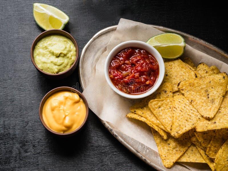 Les nachos mexicains ébrèche dans une boîte en bois avec de la sauce à Salsa, sauce à sauce au fromage et à guacamole et tranche  photos stock