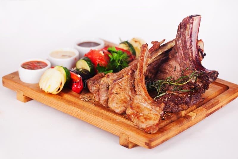 Les nervures avec le barbecue de romarin et de légume grillent, menu blanc d'isolement de fond de panneau en bois de sauces image libre de droits